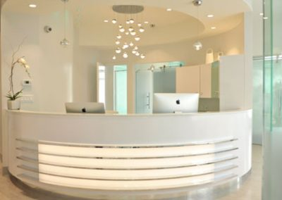Modern front desk with silver accents and tiered lighting