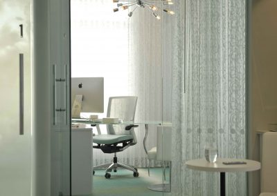 Private office with sheer drapery and sliding glass door