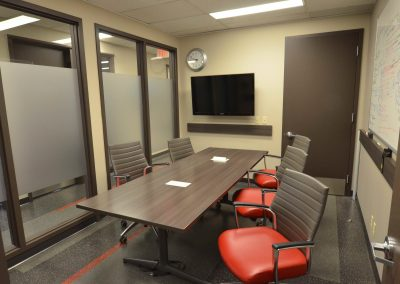 Private meeting room with boardroom and custom red chairs