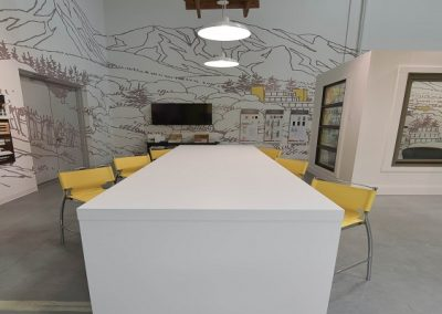 Large white communal table with custom yellow bar chairs
