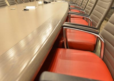 Boardroom with large meeting table and custom red boardroom chairs