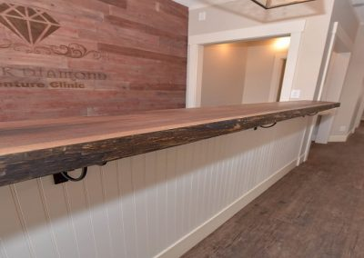 Reception area wooden front desk matching wooden feature wall
