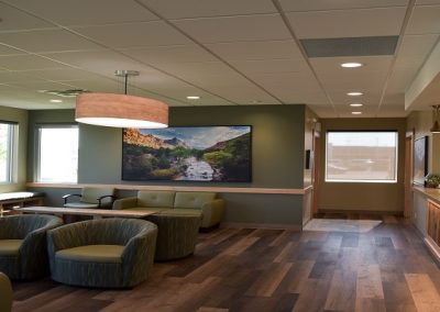 Wooden floors and stone fireplace in dentist office waiting room