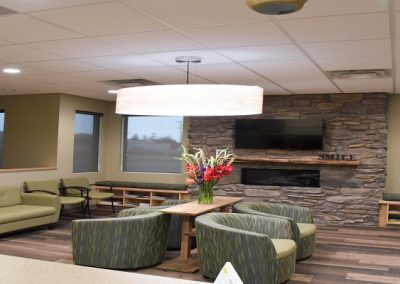 Dental office waiting room that has large stone fireplace and stylish green couches