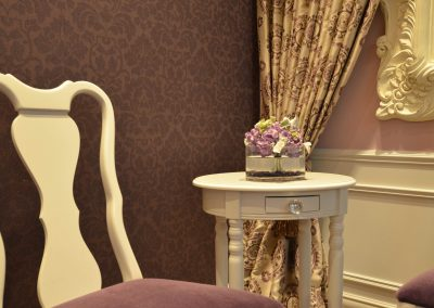 Violet damask wallpaper with matching violet velvet chairs and white side table