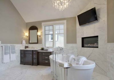 White soaker bathtub placed next to built in fireplace and large tv
