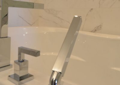 White tub fitted with modern silver bathtub faucets