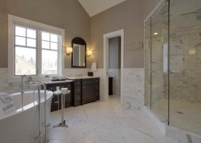 Large white themed master bathroom with window letting in light through window