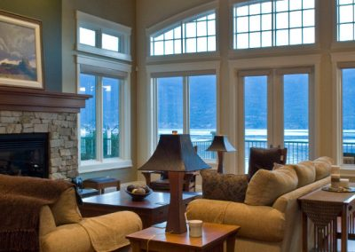 Living room with stone fireplace and lake view