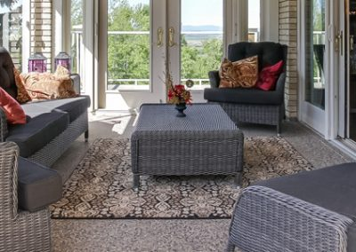 Patio furniture displayed in sunroom attached to house