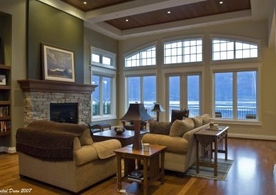 Seating area in great room with view of the lake through large arching windows