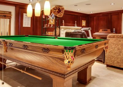 Large pool table and big screen tv in entertaining area of basement