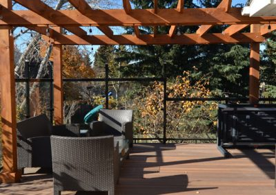 Wooden pergola above patio with glass railings
