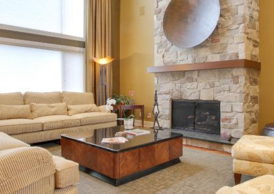 Living room with couches and large floor to ceiling stone fireplace