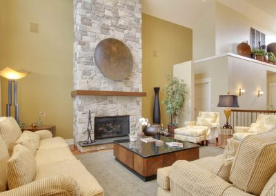 Living room with large floor to ceiling stone fireplace as focal point