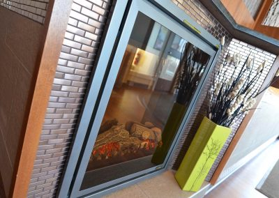 Glass fireplace surrounded by mosaic tiles