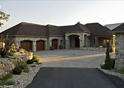 Residential exterior of custom home design with large driveway leading up to house