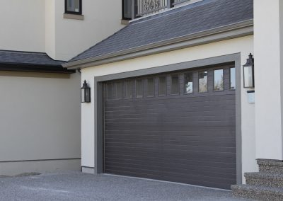 Dark brown garage door with individual small windows at the top of the door