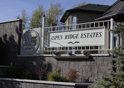 Aspen Ridge Estates sign on community fence surrounded grey bricks