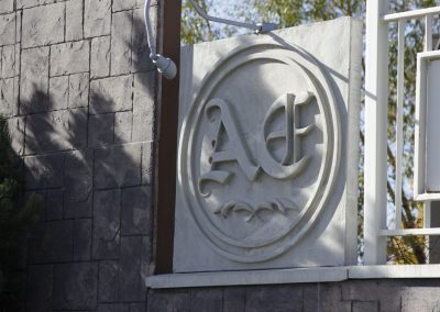 Close up of Aspen Ridge Estates logo on white cement fence