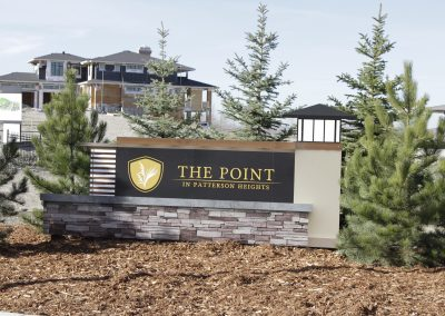 The Point in Patterson Heights community sign surrounded by small pine trees