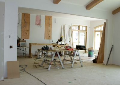 Kitchen renovation in progress with drywall present and a table of construction tools