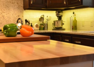 Island with wooden counter top and cutting board with peppers and knife