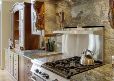 Granite backsplash surrounding stainless steel oven top