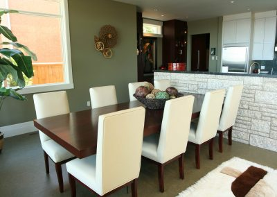 Wooden dining room table and white upholstered dining room chairs
