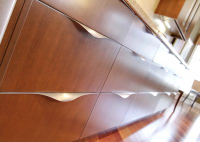 Custom wooden kitchen drawers with brushed stainless steel handles