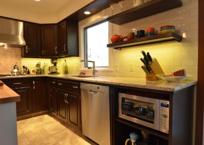 Dark cherry wood kitchen cabinets designed with white granite countertops