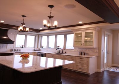 Open concept kitchen with large island and custom white cabinets
