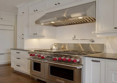 Wolf oven surrounded by custom white kitchen cabinets