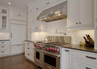 Residential kitchen renovation with white backsplash and matching white custom cabinets
