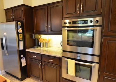 Residential Kitchen 50 Dark Wooden Cabinets and Stainless Steel Appliances