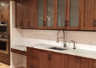 kitchen renovation with dark cabinets and modern handles with large white tiles under cabinets as back splash