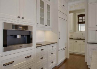Custom white kitchen cabinet design with matching white fridge