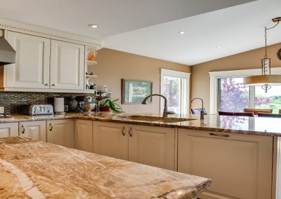 large quartz island surrounded by marble kitchen flooring