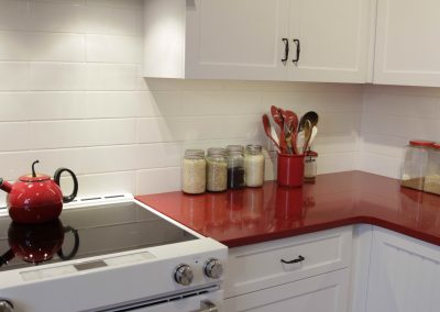 Red kitchen countertops accompanied by custom white cabinets
